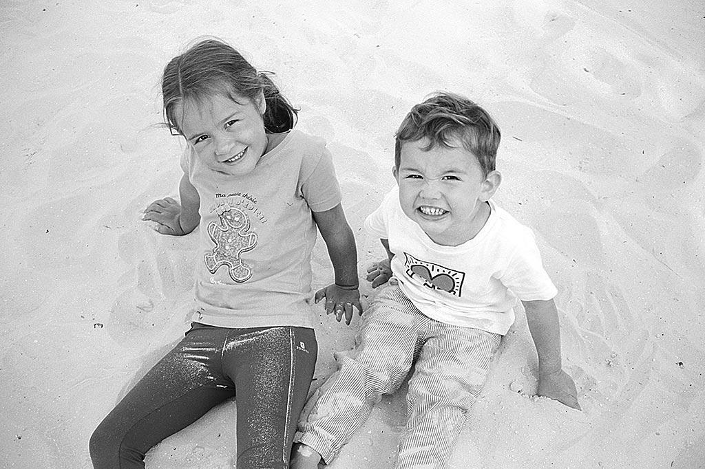 Enfants assis dans le sable. Ricoh 500G et film Kodak 100 TMax développé avec du D76.